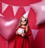 Λατρευτό όμορφο κορίτσι με τα ρόδινα μπαλόνια και το κόκκινο παρόν δώρο και τα γενέθλια ΚΑΠ Στοκ εικόνα με δικαίωμα ελεύθερης χρήσης