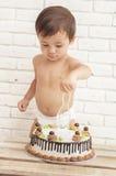 Λατρευτό όμορφο μικρό παιδί που προσπαθεί να κόψει το κέικ του Στοκ εικόνα με δικαίωμα ελεύθερης χρήσης