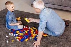 Λατρευτό grandpa που βοηθά το εγγόνι του κατά τη διάρκεια του παιχνιδιού Στοκ εικόνες με δικαίωμα ελεύθερης χρήσης