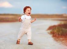 Λατρευτό redhead αγοράκι μικρών παιδιών στο jumpsuit που τρέχει μέσω του θερινών δρόμου και του τομέα Στοκ φωτογραφίες με δικαίωμα ελεύθερης χρήσης