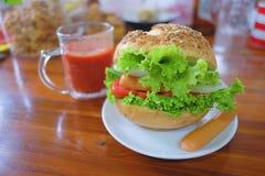 Λαχανικά και Burger λουκάνικων με το χυμό ντοματών Στοκ φωτογραφία με δικαίωμα ελεύθερης χρήσης