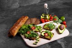 Λαχανικά κοντά στο ψωμί και το βάζο της σάλτσας σε ένα υπόβαθρο πετρών Σάντουιτς με τις ντομάτες, το αβοκάντο και τα πράσινα διάσ Στοκ φωτογραφία με δικαίωμα ελεύθερης χρήσης
