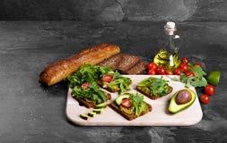 Λαχανικά κοντά στο ψωμί και το βάζο της σάλτσας σε ένα υπόβαθρο πετρών Σάντουιτς με τις ντομάτες, το αβοκάντο και τα πράσινα διάσ Στοκ Εικόνα