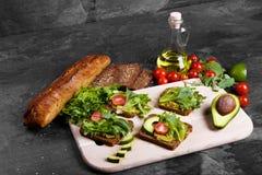 Λαχανικά κοντά στο ψωμί και το βάζο της σάλτσας σε ένα υπόβαθρο πετρών Σάντουιτς με τις ντομάτες, το αβοκάντο και τα πράσινα διάσ Στοκ Εικόνες