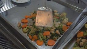 Λαχανικά μαγείρων σε ένα τηγανίζοντας τηγάνι κλείστε επάνω απόθεμα βίντεο