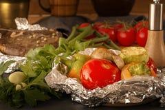 Λαχανικά που ψήνονται στο σωρό φύλλων αλουμινίου και κρέατος σε έναν ξύλινο πίνακα με τις φρέσκες ντομάτες και τα πράσινα σε ένα  στοκ φωτογραφία