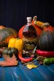 Λαχανικά πτώσης έννοιας με το μπουκάλι του πικάντικου ελαιολάδου Στοκ Εικόνα