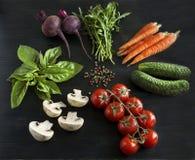Λαχανικά σε ένα μαύρο ξύλινο υπόβαθρο Στοκ Εικόνες