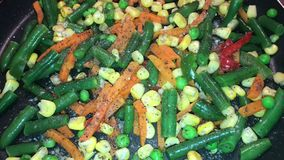 Λαχανικά σε ένα τηγάνι, που καρυκεύεται με το άλας απόθεμα βίντεο