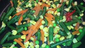 Λαχανικά σε ένα skillet που ψεκάζεται με το καρύκευμα απόθεμα βίντεο