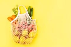 Λαχανικά στην τσάντα αγορών υφάσματος στο κίτρινο υπόβαθρο στοκ εικόνα
