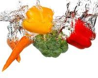 Λαχανικά στον παφλασμό νερού η ανασκόπηση απομόνωσε το λευκό Στοκ Φωτογραφίες