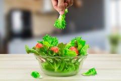 Λαχανικό σαλάτας εκμετάλλευσης χεριών ατόμων ` s επάνω από το κύπελλο γυαλιού λαχανικών σαλάτας στον ξύλινο πίνακα στην άσπρη πλά Στοκ εικόνες με δικαίωμα ελεύθερης χρήσης