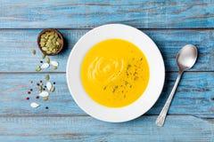 Λαχανικό φθινοπώρου ή σούπα κολοκύθας με τους σπόρους στο άσπρο κύπελλο στην ξύλινη τυρκουάζ άποψη επιτραπέζιων κορυφών στοκ φωτογραφίες