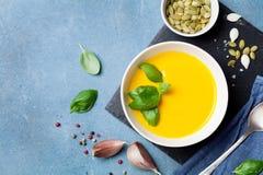 Λαχανικό φθινοπώρου ή σούπα κολοκύθας στο άσπρο κύπελλο στην μπλε άποψη επιτραπέζιων κορυφών στοκ εικόνα με δικαίωμα ελεύθερης χρήσης