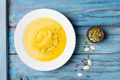 Λαχανικό φθινοπώρου ή σούπα κολοκύθας στο άσπρο κύπελλο στην ξύλινη τυρκουάζ άποψη επιτραπέζιων κορυφών στοκ φωτογραφία