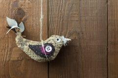 Λαϊκή διακόσμηση πουλιών τέχνης κρεμώντας σε ένα ξύλινο υπόβαθρο Στοκ Εικόνα
