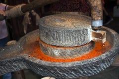 Λείανση των ξηρών κόκκινων τσίλι σε έναν μύλο πετρών στοκ εικόνες με δικαίωμα ελεύθερης χρήσης