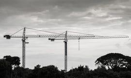 Λειτουργία γερανών στο κτήριο για την ανύψωση των εργαλείων για την εργασία εγκαταστάσεων, τη Οικοδομική Βιομηχανία στην πόλη και Στοκ Φωτογραφία