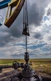 Λειτουργούντα πετρέλαιο και φυσικό αέριο που σχεδιάζουν περίγραμμα καλά στο νεφελώδη ουρανό στοκ εικόνα