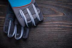 Λειτουργώντας γάντια κηπουρικής στην εκλεκτής ποιότητας ξύλινη γεωργία πινάκων con Στοκ φωτογραφία με δικαίωμα ελεύθερης χρήσης