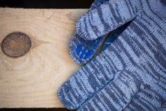 Λειτουργώντας γάντια στο βιομηχανικό ξύλο Στοκ εικόνα με δικαίωμα ελεύθερης χρήσης