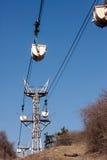 Λειτουργώντας εναέριος σιδηρόδρομος καλωδίων στο υπόβαθρο του μπλε ουρανού Στοκ Φωτογραφίες