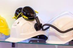 Λειτουργώντας κράνη για να προστατεύσει τους οικοδόμους με τα ακουστικά και ένα headla στοκ φωτογραφίες