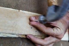Λειτουργώντας μόριο χεριών ατόμων ένα σφυρί στο ξύλο Στοκ φωτογραφίες με δικαίωμα ελεύθερης χρήσης