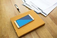 Λειτουργώντας πίνακας με το σημειωματάριο, τη μάνδρα, το έγγραφο και το smartphone Ξύλινο επιτραπέζιο υπόβαθρο στοκ εικόνες