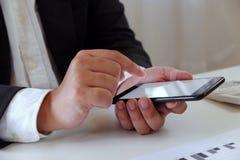 Λειτουργώντας στην αρχή χρησιμοποιώντας κινητό τηλέφωνο επιχειρηματιών στο γραφείο στοκ εικόνες