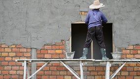 Λειτουργώντας τοίχος ασβεστοκονιάματος εργασίας στο εργοτάξιο οικοδομής απόθεμα βίντεο