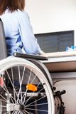 Λειτουργώντας υπολογιστής γραφείων γραφείων αναπηρικών καρεκλών συνεδρίασης άκυρων ή με ειδικές ανάγκες γυναικών Στοκ εικόνες με δικαίωμα ελεύθερης χρήσης