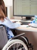 Λειτουργώντας υπολογιστής γραφείων γραφείων αναπηρικών καρεκλών συνεδρίασης άκυρων ή με ειδικές ανάγκες γυναικών Στοκ φωτογραφία με δικαίωμα ελεύθερης χρήσης