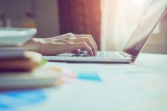Λειτουργώντας lap-top χεριών επιχειρηματιών στο ξύλινο γραφείο στην αρχή στο φως πρωινού Στοκ Φωτογραφία