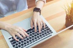 Λειτουργώντας lap-top χεριών επιχειρηματιών στο ξύλινο γραφείο στην αρχή και το ψηφιακό ρολόι ένδυσης Εκλεκτής ποιότητας επίδραση Στοκ Εικόνες