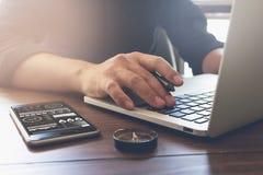 Λειτουργώντας lap-top χεριών επιχειρηματιών στο ξύλινο γραφείο στην αρχή στο φως πρωινού Στοκ Εικόνες