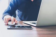 Λειτουργώντας lap-top χεριών επιχειρηματιών στο ξύλινο γραφείο στην αρχή στο φως πρωινού Στοκ φωτογραφία με δικαίωμα ελεύθερης χρήσης