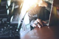 Λειτουργώντας lap-top χεριών σχεδιαστών με το πρώτο πλάνο πράσινων εγκαταστάσεων στο ξύλο Στοκ εικόνα με δικαίωμα ελεύθερης χρήσης