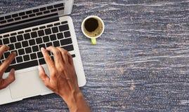 Λειτουργώντας lap-top χεριών comuter με το φλιτζάνι του καφέ Στοκ Εικόνα