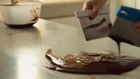 Λειωμένη σκοτεινή σοκολάτα που αναμιγνύει σε έναν πίνακα απόθεμα βίντεο