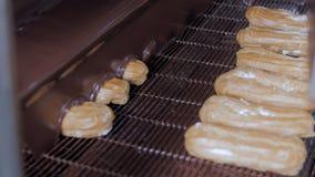 Λειωμένη σοκολάτα που ρέει στα φρέσκα κρεμώδη κέικ ECLAIR σε έναν μεταφορέα σε ένα αρτοποιείο απόθεμα βίντεο