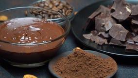 Λειωμένο σοκολάτα ή φουντούκι που διαδίδεται στα κομμάτια κύπελλων και σοκολάτας γυαλιού στο σκοτεινό συγκεκριμένο υπόβαθρο φιλμ μικρού μήκους