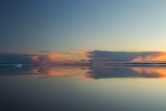 Λειώνοντας λίμνη βουνών άνοιξη στον ήλιο ρύθμισης Στοκ Εικόνες