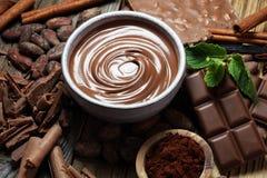 Λειώνοντας σοκολάτα ή λειωμένη σοκολάτα με έναν στρόβιλο σοκολάτας Μ στοκ εικόνα