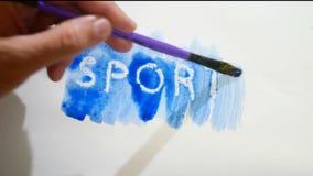 Λεκές χρωμάτων καλλιτεχνών watercolor επιγραφής αθλητικών κειμένων που απομονώνεται στο άσπρο βίντεο τέχνης υποβάθρου Στοκ φωτογραφίες με δικαίωμα ελεύθερης χρήσης