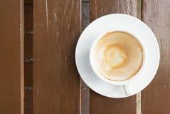 Λεκέδες καφέ σε ένα φλιτζάνι του καφέ στον ξύλινο πίνακα Στοκ Φωτογραφίες