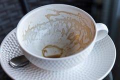 Λεκέδες καφέ σε ένα φλιτζάνι του καφέ στο μαύρο γυαλί Στοκ Φωτογραφία