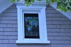Λεκιασμένο αττικό παράθυρο γυαλιού σε ένα εξοχικό σπίτι στοκ εικόνες με δικαίωμα ελεύθερης χρήσης