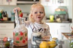 Λεμονάδα ανακατώματος μικρών κοριτσιών στο μετρητή κουζινών Στοκ φωτογραφία με δικαίωμα ελεύθερης χρήσης